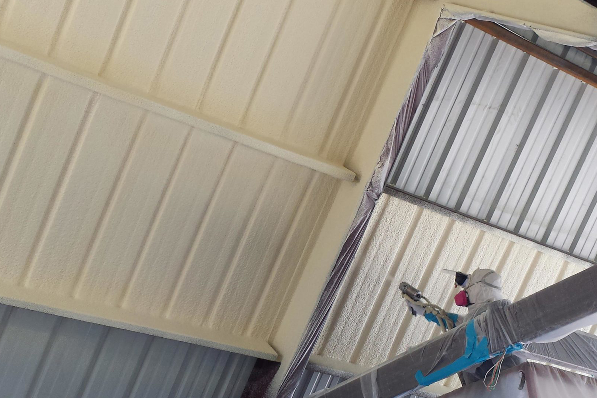 Spraying foam on inside commercial roof warehouse