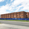 brown brick building with blue construction fencing